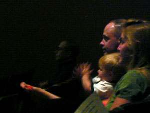 A young audience member applauds